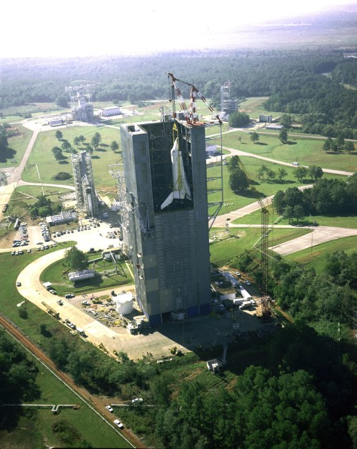 This aerial view of the shuttle Enterprise from 1978 shows the shuttle orbiter being hoisted into Marshall's Dynamic Test Stand for the Mated Vertical Ground Vibration test. The test marked the first time that the entire space shuttle -- an orbiter, an external tank and two solid rocket boosters -- were mated together. The purpose of the vibration tests was to verify whether the shuttle performed its launch configuration as predicted. (NASA, Wikipedia)