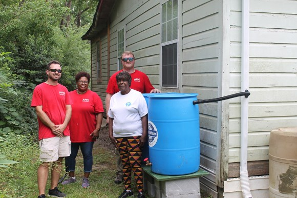 Volunteers from the Alabama Power Service Organization pose for a picture with a homeowner after installing rain barrels at her home in Prichard. (Beth Thomas / Alabama Power)