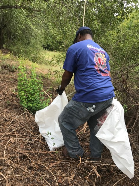 A volunteer picks up trash near Valley Creek. (Michael Sznajderman/Alabama NewsCenter)