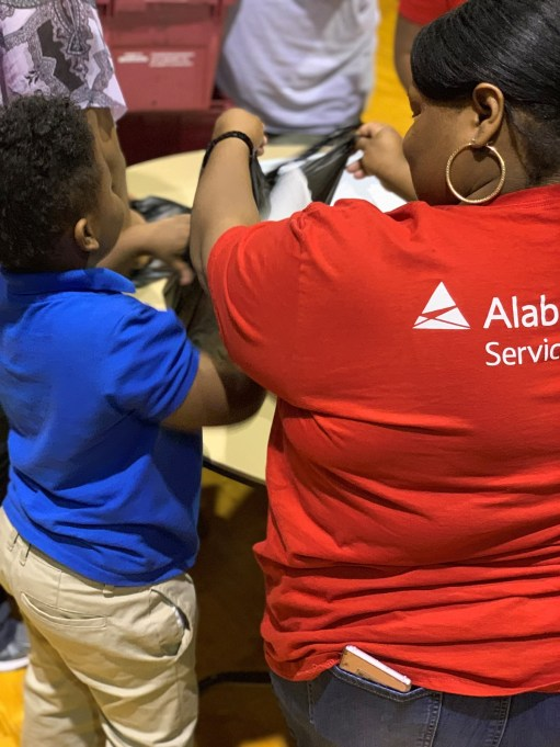 Alabama Power Service Organization member Shenita Baker and her son were among hundreds of volunteers recently packed bags for Huetytown Community Helpers' Blessings in a Bag program. (Morgan Jackson / Alabama NewsCenter)