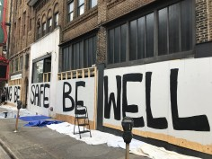 Volunteers paint an inspirational message on the boards covering the windows and doors of the Alabama Theatre. (Michael Sznajderman/Alabama NewsCenter)