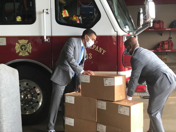 Montgomery Mayor Steven Reed, left, and retired Brig. Gen. Trent Edwards stack a box of face shields. AFLAC donated 10,000 face shields to the region . (Michael Jordan / Alabama NewsCenter)