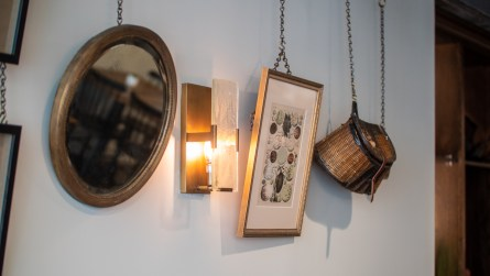 In the long, narrow dining room downstairs, an art wall showcases a diverse collection, from tortoise shells and paintings and prints to turkey feathers and handmade baskets. (Dennis Washington / Alabama NewsCenter)
