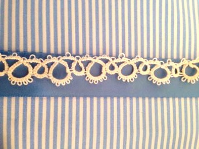 Tatted cotton lace against blue satin ribbon