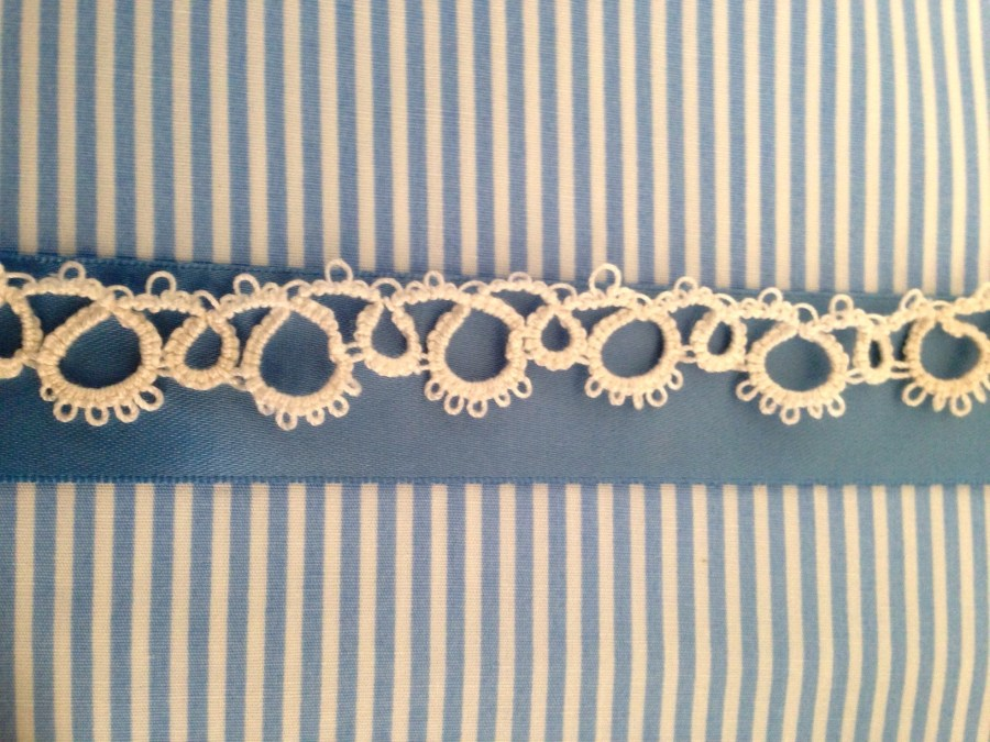 White tatted lace against blue satin ribbon