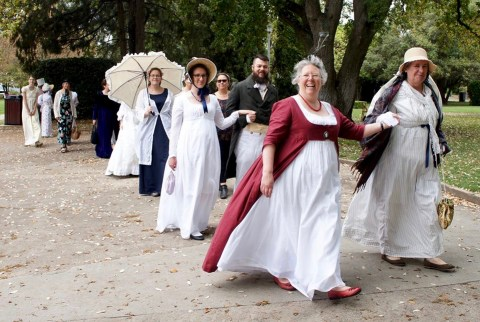 Group of ladies and a few gents in Regency costumes promenading in a park.