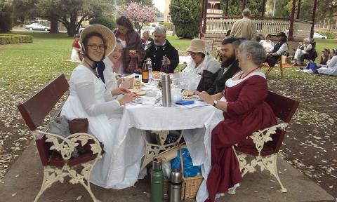 people in costume eating at an elegantly-set picnic table in a park