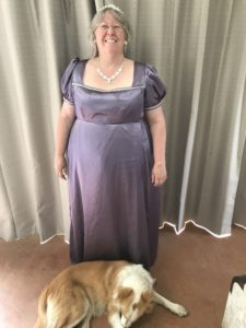 Bron wearing a mauve satin Regency ball-gown with Pippin the border-collie at her feet