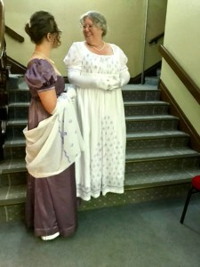 Lauren in a mauve satin dress and Bronwyn in a white muslin-blockprint dress