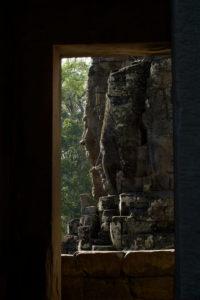 Visages de pierre du Bayon vu à travers une porte