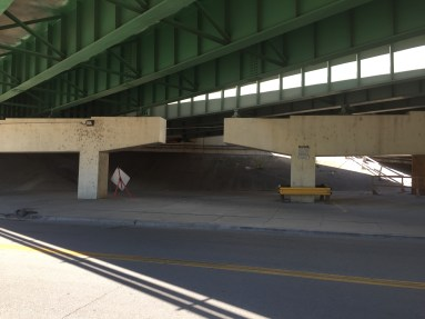 Homeless people sleep at the top of sloped concrete just under the highway and out of view unless you're walking and looking for them.