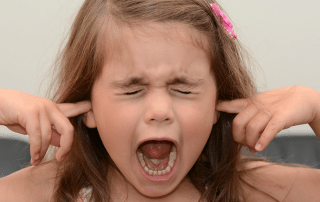 Girl screaming with fingers in her ears