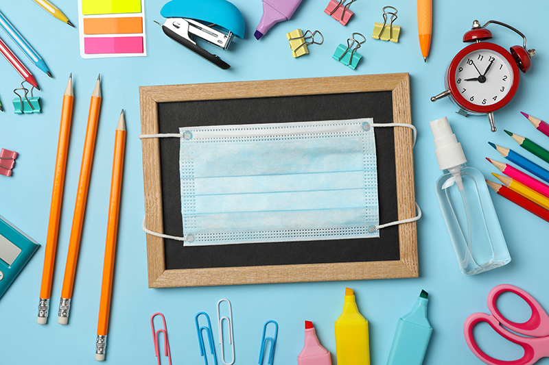 School supplies with medical mask and sanitizer on blue backgrou
