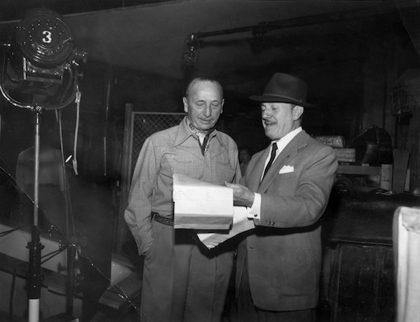 photo of michael curtiz and jack l warner reviewing script on movie set