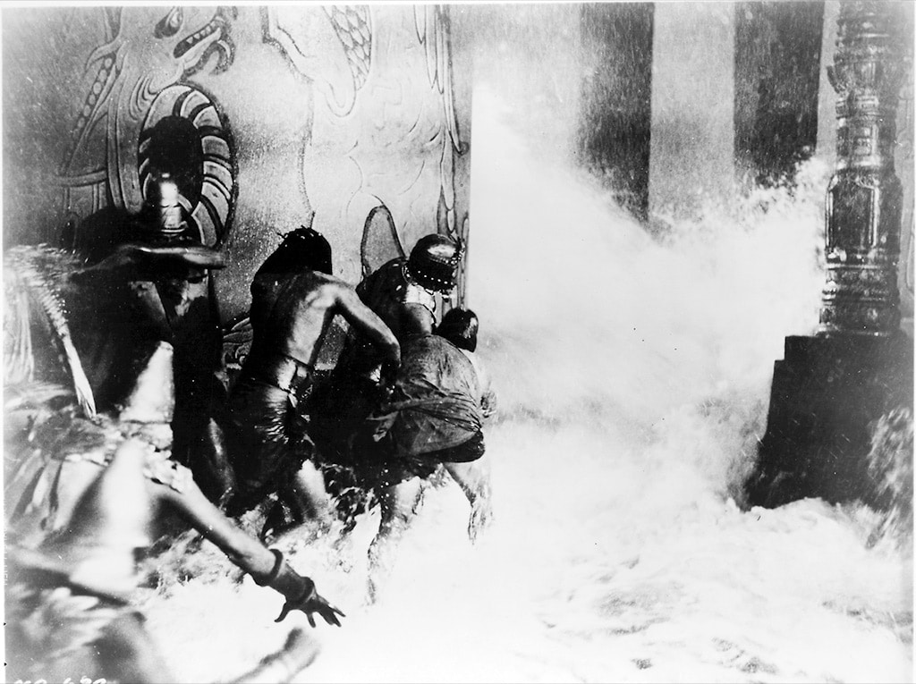 Noah's Ark flood scene - black and white still from 1928 classic showing millions of gallons of water pouring down on extras in costume