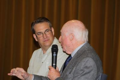 photo of Norman Lloyd and Alan K. Rode on stage as Norman speaks into microphone