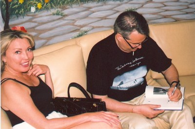 photo of Anita Carson seated with Alan K. Rode as he signs a copy of his book for her