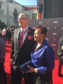 photo of Alan K. Rode and Jemma Rode pose for photos on red carpet in front of Chinese Theatre