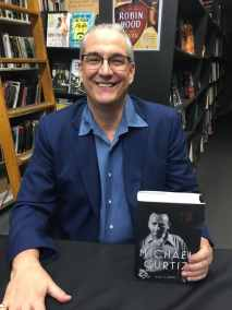 photo of Alan K. Rode at book-signing event holding copy of his Michael Curtiz biography hard cover book