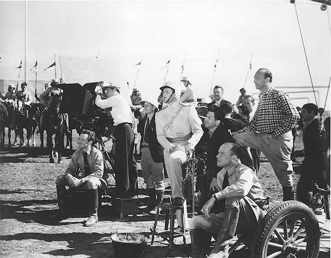 photo of film crew on exterior location with actor Errol Flynn and director Michael Curtiz standing next to movie camera and crew