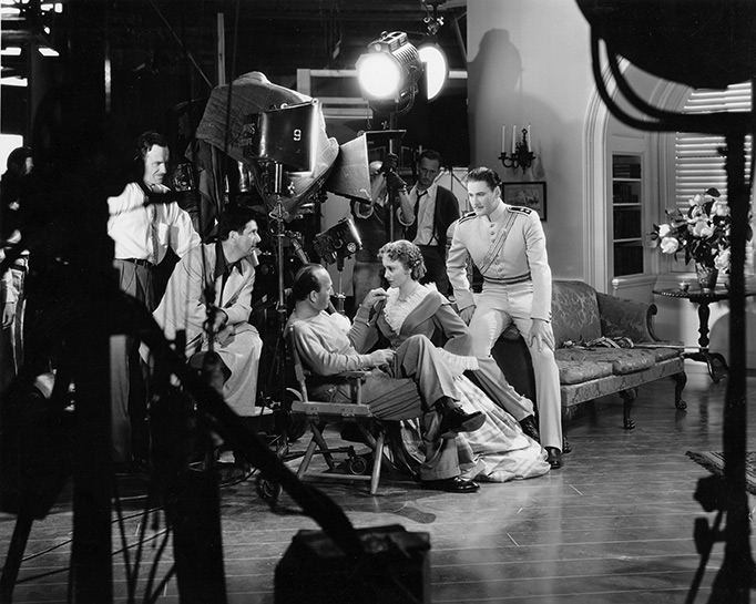 photo of movie set featuring director Michael Curtiz seated next to actress olivia de havilland with actor errol flynn standing behind de havilland