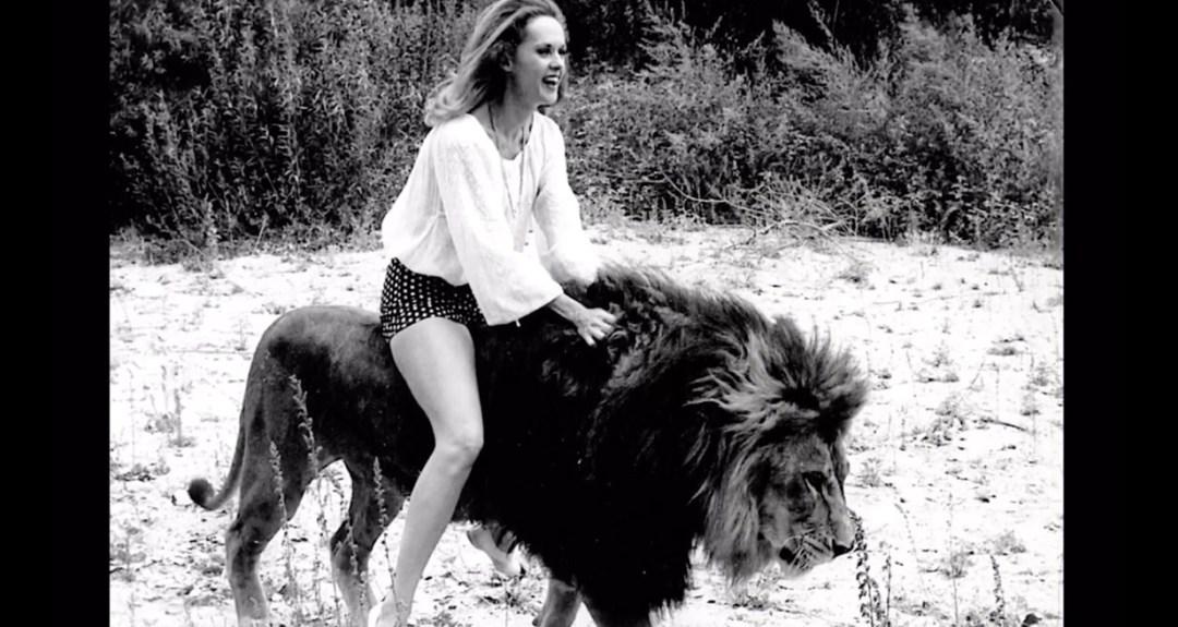 photo of Tippi Hedren riding a large lion
