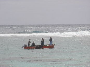 Fishermen head out to the roughness at the reef fringing the lagoon