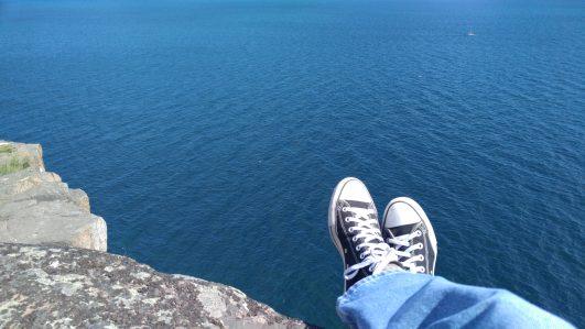 Feet overhanging cliff over water