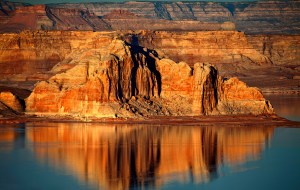 View of Lake Powell with reflection on still blue water. Bright sunset light with intense realistic sunset colors. Taken by Spokane photographer Alan Tower.