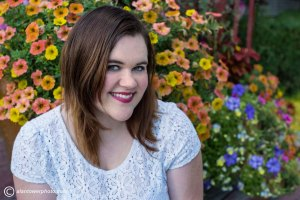 Pretty woman smiling and seated in front of yellow and russet petunias.  Spokane Photographer Alan Tower www.alantowerphoto.cm