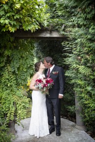 A kiss under the arbor on wedding day.