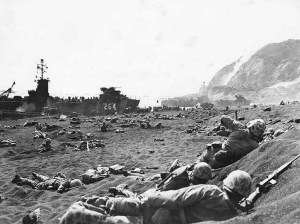Marines burrow in the volcanic sand on the beach of Iwo Jima, as their comrades unload supplies and equipment from landing vessels despite the heavy rain of artillery fire from enemy positions on Mount Suribachi in the background. Image-U.S. Military
