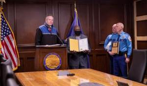 Governor Dunleavy recognizes Alaskan resident Antoine Aridou for helping Trooper Laura Reid save the life of a 12-year-old boy. Col. Doug Massie and Commissioner James Cockrell presented Aridou with a Life-Saving Award.