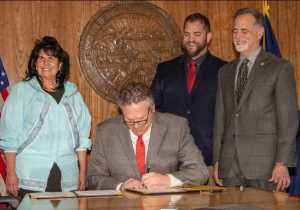 Governor Dunleavy signs a proclamation ending the COVID-19 Emergency Declaration in the Alaska State Capitol on April 30, 2021. Dunleavy is pictured with Representative Cathy Tilton, DHSS Commissioner Adam Crum, and Senator Micciche.