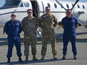 Coast Guard Lt. Cmdr. Gregory Fernley (left to right), Alaska Army National Guard Sgt. 1st Class Phillip Becton, Alaska Army National Guard Maj. Daniel Klinkner and Coast Guard Cmdr. Jereme Altendorf take a moment for a photo in front of an Alaska Army National Guard C-12J Huron aircraft. U.S. Coast Guard photo by Petty Officer 1st Class Nate Littlejohn.