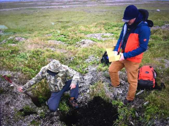 Ian Putnam (right), a Coast Guard physical scientist, and Edmund Gaines, a Coast Guard-contracted archaeological consultant, prepare to repatriate unidentified Alaska Native remains at Point Spencer, Alaska, Aug. 12, 2021. The two returned the remains to the site where they'd been accidentally collected during an archaeological excavation on Coast Guard-owned property, near the former Long Range Aids to Navigation (LORAN) C Station at Port Clarence. Image-Petty Officer 1st Class Nate Littlejohn