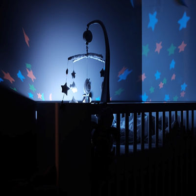 A crib lit by a hanging mobile
