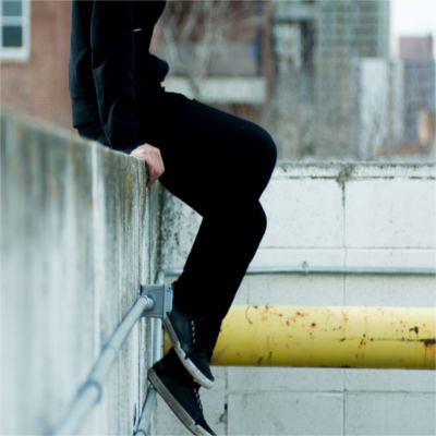 Person sitting on cement wall
