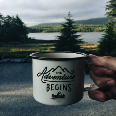 """A coffee cup that says """"The Adventure Begins"""""""