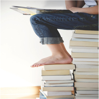 A person sitting on a stack of books