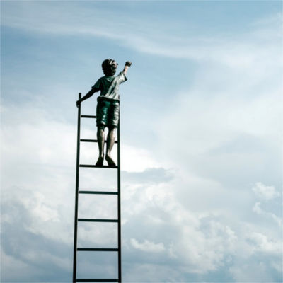 A child at the top of a ladder, reaching toward the sky
