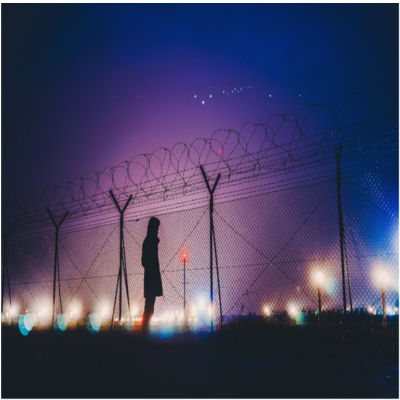 A person standing outside a person fence at night
