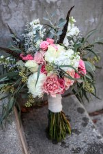 Shabby chic bridal bouquet made with eucalyptus, feathers, carnations, football mums, roses, stock and spray roses   designed by Natasha Price of Alaskaknitnat.com