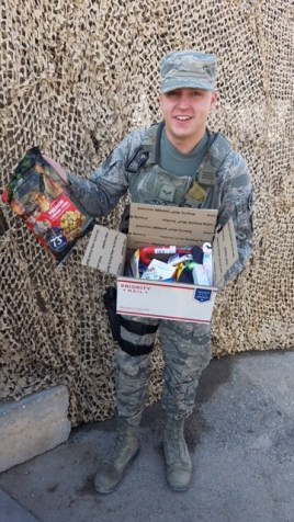 Airmen shows contents of care package.