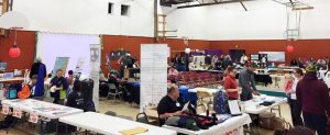 large gymnasium with vendor tables