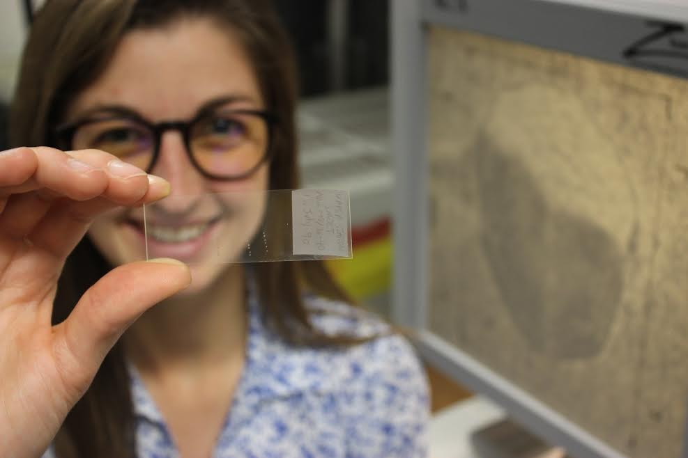 woman with glasses holding up a microscope slide
