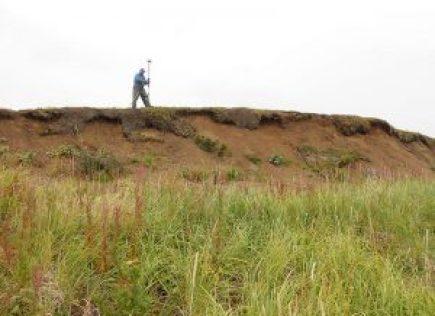 Man standing on ridge with scientific equipment