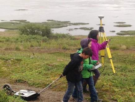 Three children walking on gravel road with scientific equipment