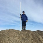 Man standing on berm with tall measuring stick
