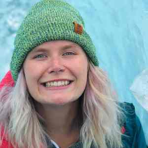 Young woman with long blonde hair and green knit cap smiling, with glacier ice in the background